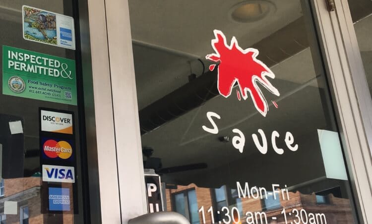 The front window and door of Sauce restaurant in Bridgeville.