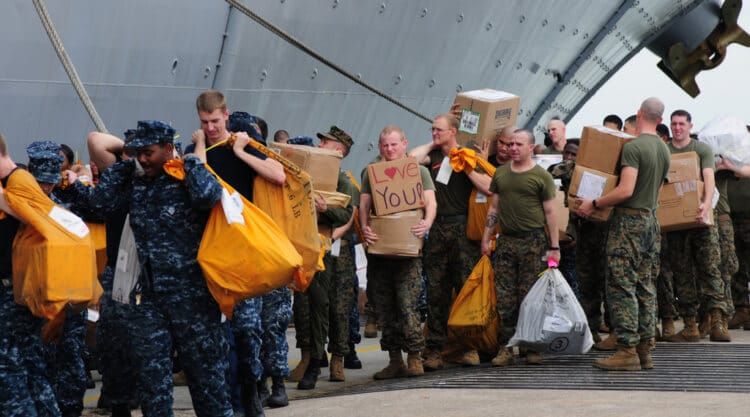 Sailors and Marines move mail onto the amphibious assault ship USS Makin Island.