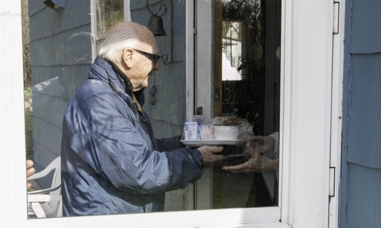 "Connecticut State Senator Joe Crisco helped deliver prepared meals to homebound residents of Naugatuck as part of the New Opportunities, Inc. ""Meals on Wheels"" program."