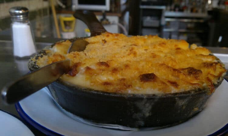 A bowl of macaroni and cheese sits atop a restaurant plate