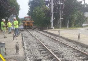 Construction workers stand alongside railroad tracks as part of a project to improve the railroad crossing at Bower Hill Road and Railroad Street in Bridgeville.