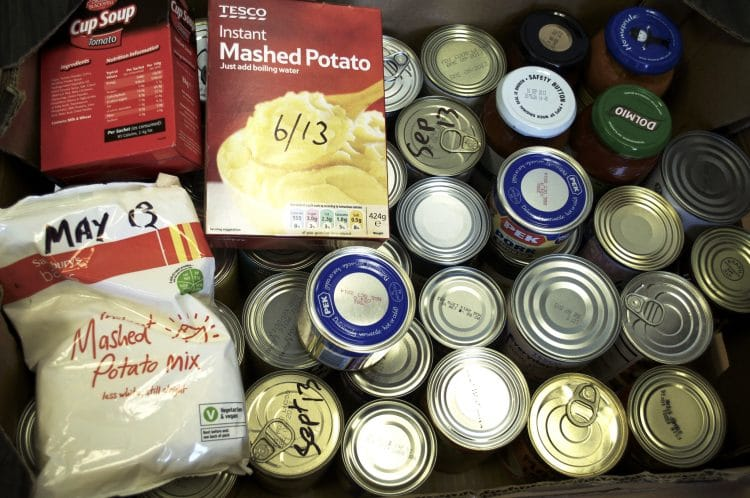 A food bank donation box filled with canned goods and other non-perishable items