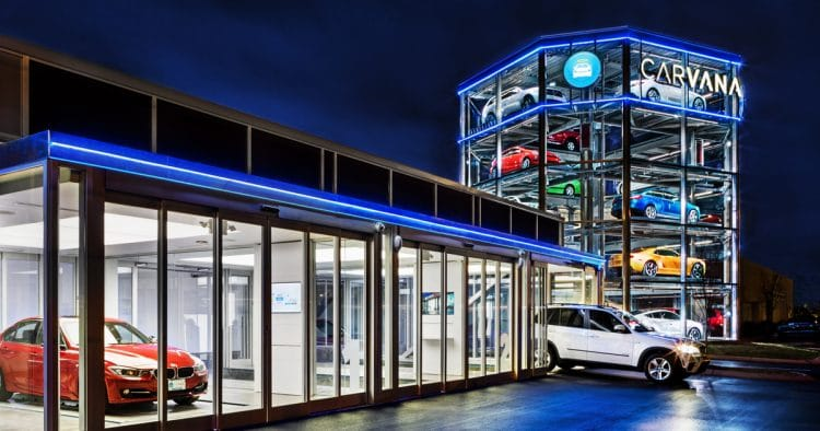 "An illustration of a Carvana dealership at night, with a ""vending machine"" tower filled with cars"