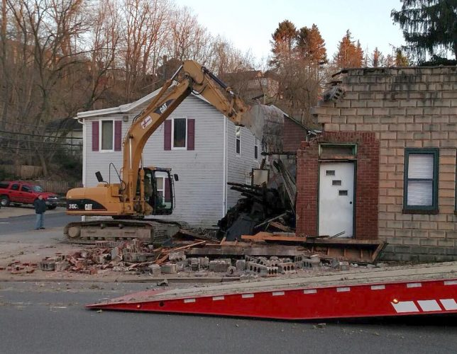 A bulldozer is shown demolishing the building at 686 Baldwin Street in Bridgeville, PA.